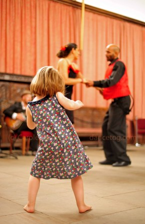 A little girl learns the moves in an adult's swing class
