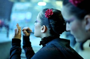 two young people applying cosmetics in preparation for their performance at 2010's Danzainfiera