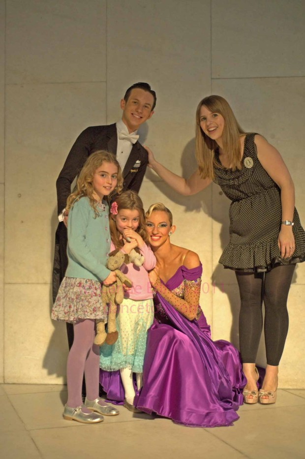 two little girls posing with their ballroom heroes