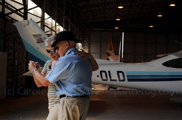 Two older people dancing tango in front of a small private plane