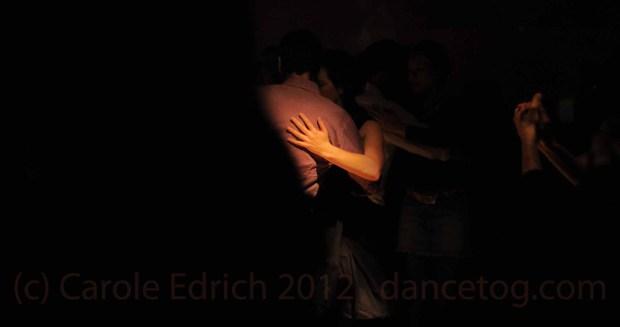 Couple dancing tango through a pool of light