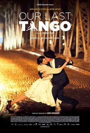 Photograph of a male and female danging tango in close embrace. They are on a large bridge or portway with building in the background, the light is golden suggesting it is night time and while the two are dancing close together (the man is dragging the woman) they somehow don't look close.