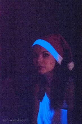 Girl with large eyes wearing a Christmas hat and white toga-style top. You can tell it is very dark because the image is extremely grainy, there is considerable colour noise and the colours are not true.