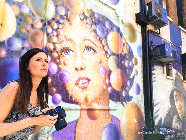 Lady with long dark hair stares intently ahead and to the right of the image. She has a camera in her hand but it's pointing down. Behind her is a beautiful mural depicting a beautiful woman surrounded by unexplained baubles of many colours, also staring into the distance this time to the left of the image. In the further distance is another mural of a dark skinned boy with sad eyes who is wearing a hoodie.