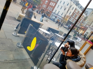 Young olive skinned girl crouching by partially shown stools with an intent look on her face as she takes a photograph through a window. It looks cold and bright outside, there are people walking past and the butterfly logo of Itsu is clearly visible on a temporary fence around tables