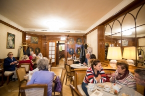 Image showing bustling coffee shop in Vienna. Mostly wome of all ages are talking intently to each other in an opulent surrounding that is light and airy, the closest woman with her back to us has grey shoulder length hair and is reading an Austrian language paper and two women aged between 18 and 20 are talking to each other around a table facing us. Towards the far end of the room is a rack of newspapers and the general feeling of the room is that it is one of many.