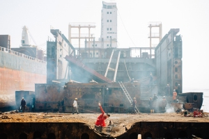 Foreground is dusty, sand, with small concave depression right in the centre at the bottom of the shot. Manuela, a dark-haired Latin looking woman is dancing with one arm benind her exactly parallel to a ladder some distance behind her. This ladder leads to what appears to be an abandoned building behind which are the remnants of what appears to be either a huge ship or a 10-12 storey narrow tower block. In the middle ground are several people ship-breaking, working in the skeleton of the ship,
