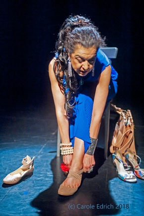 Lady dressed artistically with long dark hair and blue driess pulling on flat dance shoes while seated. A handbag and tall tango shoes are to her left (our right) and the other flat ballet shoe to her right
