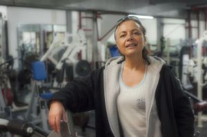 a slightly tanned white woman lifts her chin and smiles at the photographer. In the background is a hard core bodybuilding gym.