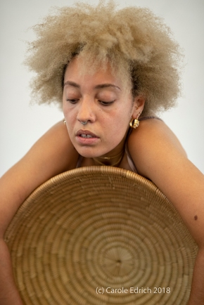 Sad, tired lady of Caribban background rests or cuddles a large empty woven basked. Her eyes are closed, her hair is loose and she is wearking gold hoop earrings iwth a complex design.