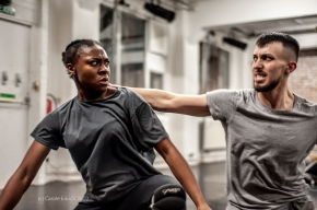 two dancers, a black woman and white man stare agreesively at each other. He has a hand on her neck. She is bent away from him
