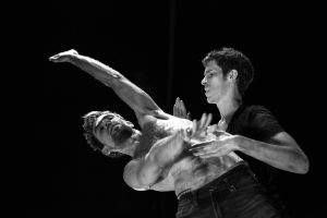 Black and white image with two men dancing, one without a top, one is reaching sideways the other is gazing at him