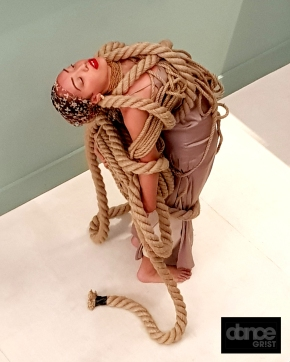 Female dancer bent backwards under the apparent weight of artistically wound ropes, her eyes are shut and she gives an aura of strength and perseverence