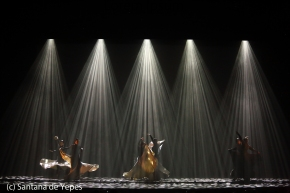 Huge stage with dancers and flaring skirts and men in black under corruscading lines of white and grey light