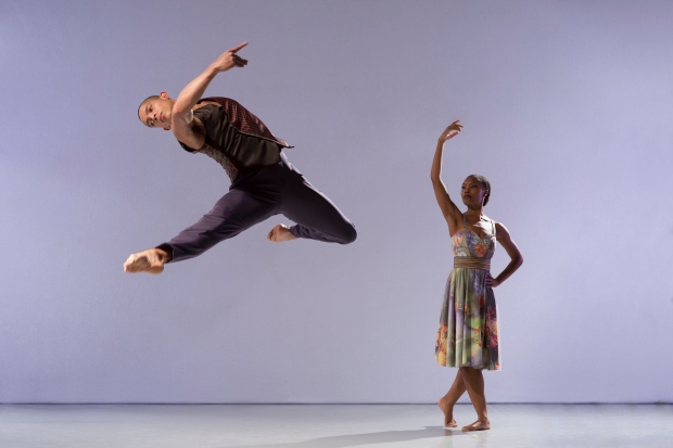 male and female dancers in studio setting, the male is jumping with legs far apart and thrown backwards